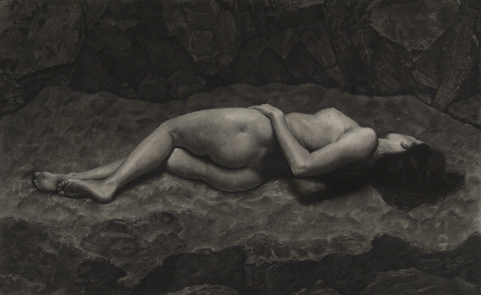 A full, large, nude figure drawing in charcoal of a woman lying on her side with her back facing the viewer. She lies on a large rock in the mountains with more rocks behind her. She appears to be relaxed and comfortable in spite of the hard, rough, and cold rock she lies upon. Overall, the general tone of the drawing is dark.